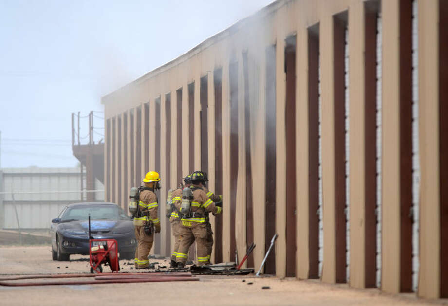 Midland emergency personnel cut their way into storage units while locating the source of a fire Saturday at 1306 W. County Rd. 114. James Durbin/Reporter-Telegram Photo: JAMES DURBIN