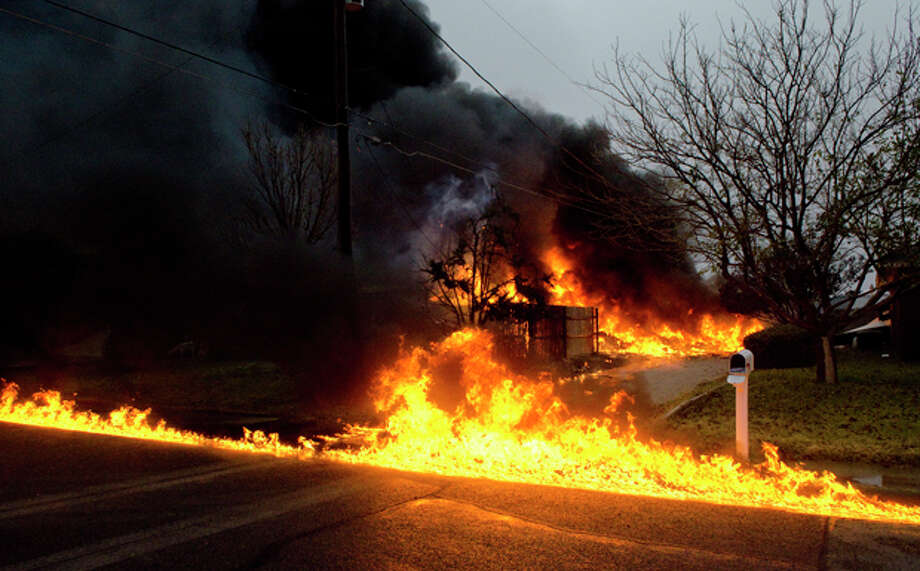 Aviation fuel burns down Casper Court following a small plane crash into a home at the corner of Casper and Trevino. Photo by Tim Fischer/Midland Reporter-Telegram Photo: Tim Fischer/Reporter-Telegram