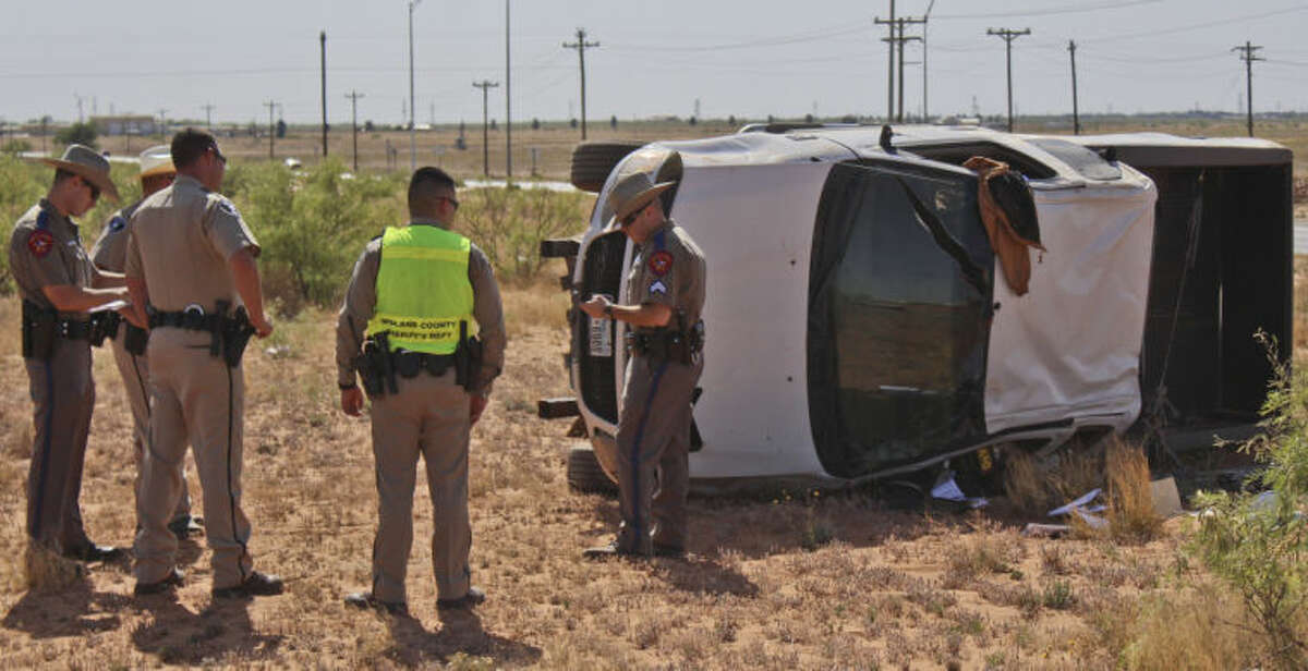 Midland County deputies and Department of Public Safety Troopers investigate this pickup rollover crash Sunday afternoon on West Loop 250 near North County Road 1150. Tyler White/Reporter-Telegram