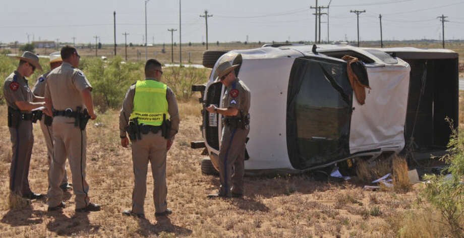 Midland County deputies and Department of Public Safety Troopers investigate this pickup rollover crash Sunday afternoon on West Loop 250 near North County Road 1150. Tyler White/Reporter-Telegram Photo: TYLER WHITE