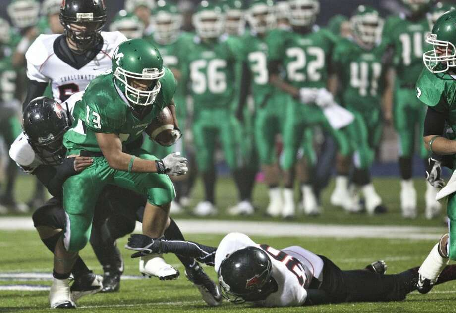 Monahans' Pedro Cano (13) drives foreward as Shallowater's Anthony Montes (44) and Freddy Garcia (30) attempt to tackle him during the Class 3A Division II state quarterfinals Friday at Grande Communications Stadium. Albert Cesare Odessa American