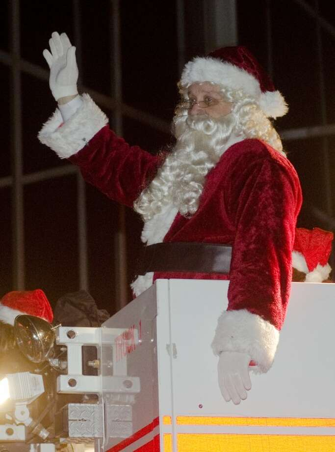 Waving from the top of a Midland fire truck, Santa helps lead the annual City Christmas Parade Saturday evening. Photo by Tim Fischer/Midland Reporter-Telegram Photo: Tim Fischer
