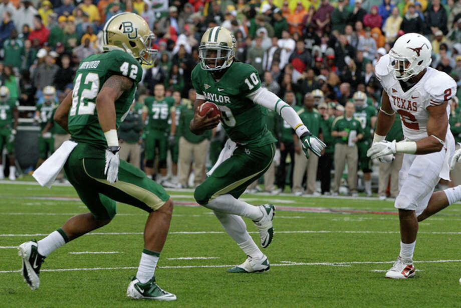 Baylor quarterback Robert Griffin III (10)finds running room as Levi Norwood (42) helps with pressure from Texas' Keenan Robinson (2) in the first half of an NCAA college football game Saturday, Dec. 3, 2011, in Waco, Texas. (AP Photo/Tony Gutierrez) Photo: Tony Gutierrez / AP