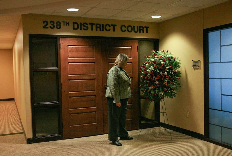 Midland County District Attorney Teresa Clingman looks at a wreath placed outside the 238th District courtroom in which Judge John Hyde presided. Hyde, 69, died Monday at Midland Memorial Hospital following a battle with cancer. Cindeka Nealy/Reporter-Telegram Photo: Cindeka Nealy