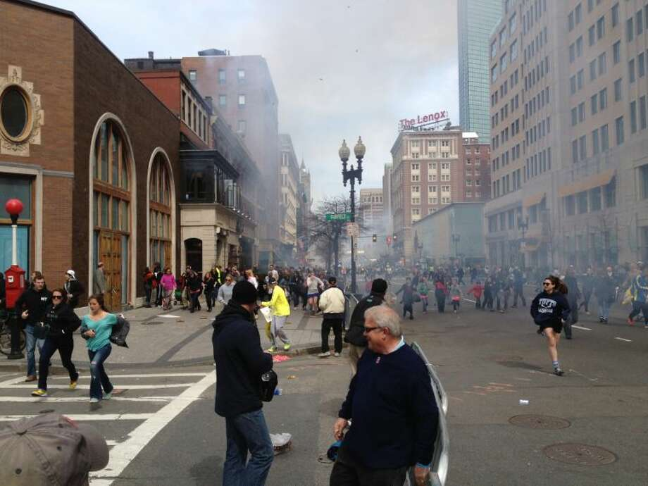 This Monday, April 15, 2013 photo shows a man who was dubbed Suspect No. 2 in the Boston Marathon bombings by law enforcement, on the left side of the frame, wearing a white baseball cap, walking away from the scene of the explosions. The FBI identified him as 19-year-old college student Dzhokhar Tsarnaev, who along with his brother Tamerlan, 26, previously known as Suspect No. 1, killed an MIT police officer, severely wounded another lawman and hurled explosives at police in a car chase and gun battle during a night of violence, early Friday, April 19, 2013. Tamerlan Tsarnaev was killed overnight, officials said, while his brother Dzhokhar remains at large. (AP Photo/David Green) EXCLUSIVE CONTENT-SPECIAL RATES APPLY FOR NON-AP MEMBERS AND SUBSCRIBERS. Photo: David Green