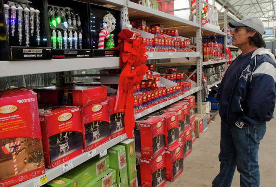 Mario Morales looks at Christmas lights Monday afternoon at Lowes after he and his wife decided to change the color scheme of their home decorations this year. Photo by Tim Fischer/Midland Reporter-Telegram Photo: Tim Fischer