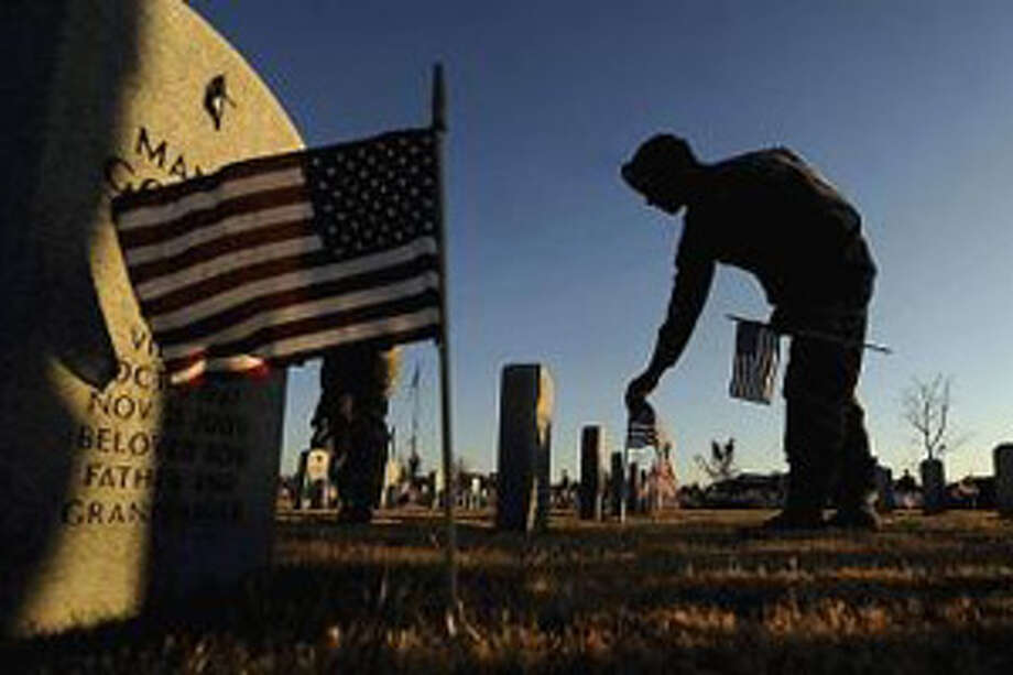 Staff Sgt. Tim Slusser puts a flag at one of the headstones at the Texas State Veterans Cemetery in Abilene, Texas in Nov. in preparation for Veteran's Day. The Washington Post says the incinerated partial remains of at least 274 American troops were sent to the King George County Landfill in Virginia. Photo: Tommy Metthe/AP
