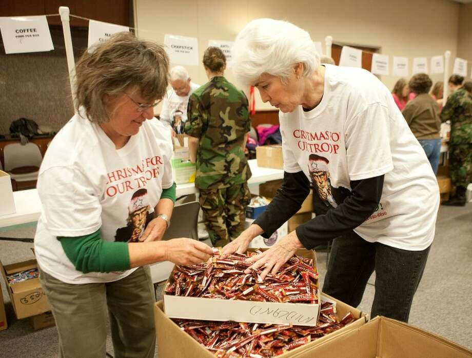 Cheryl Sellars, left, and Sharla Hotchkiss grab coffee packages to restock the Christmas for Our Troops assembly line Wednesday at First Presbyterian Church. Cindeka Nealy/Reporter-Telegram Photo: Cindeka Nealy