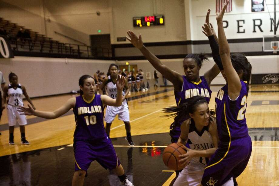 Permian's Elizabeth Aguilar (10) is trapped by Midland High's Skeesha Bowers (20) and DeSare Allen (30) during the game Tuesday at the Permian Fieldhouse. Photo: Albert Cesare/Special To The MRT