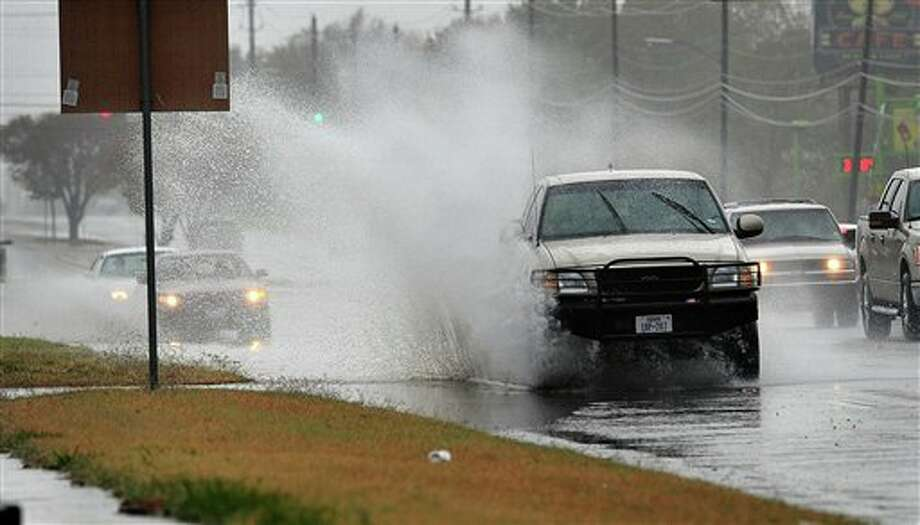 FILE - In this Nov. 21, 2011 file photo, a pickup truck splashes through a large puddle formed along Southwest Parkway in Wichita Falls, Texas, during heavy rain. Weather officials considered moving parts of North Texas into the least severe stage of drought but held off because lakes levels haven't risen from the recent rains in the area. (AP Photo/Wichita Falls Times Record News, Torin Halsey, File) Photo: Torin Halsey / AP2011