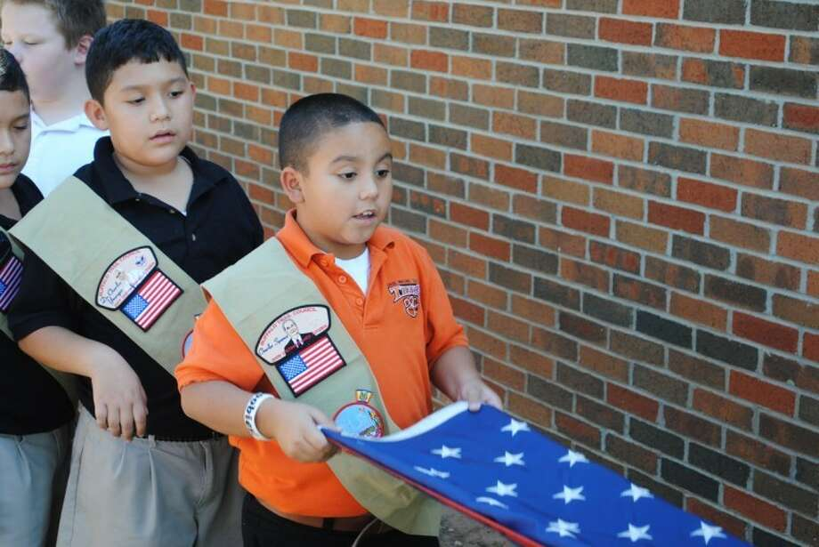 Boys in the after-school Boy Scout program at Pease Communication and Technology Academy learn about flag etiquette. Photo: Courtesy Photo