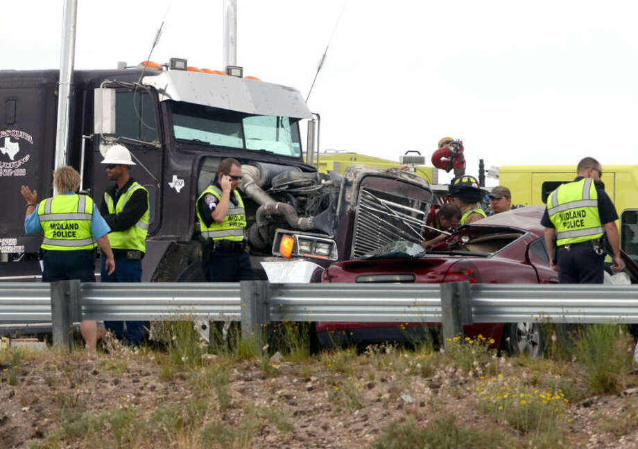 Midland emergency personnel work the scene of an accident that left one dead and two injured at the I-20 and Ranken Highway overpass Friday. James Durbin/Reporter-Telegram Photo: JAMES DURBIN