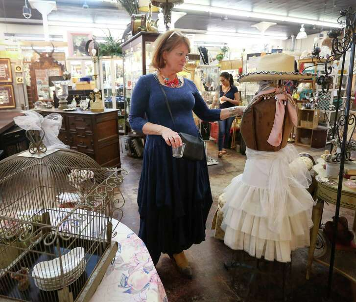 Cindy Loper, who runs a booth in AG Antiques on West 19th Street in the Heights, prepares her display.