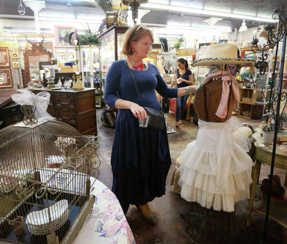 Cindy Loper, who runs a booth in AG Antiques on West 19th Street in the Heights, prepares her display. Photo: Jon Shapley, Staff / © 2015  Houston Chronicle