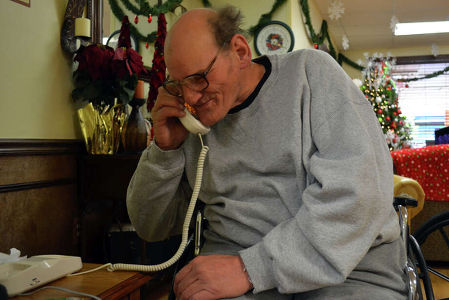 Don McGraw answers a child's phone call to Santa's Helpers Friday afternoon at the Terrace West Nursing and Rehabilitation center. Photo: James Cannon/MRT