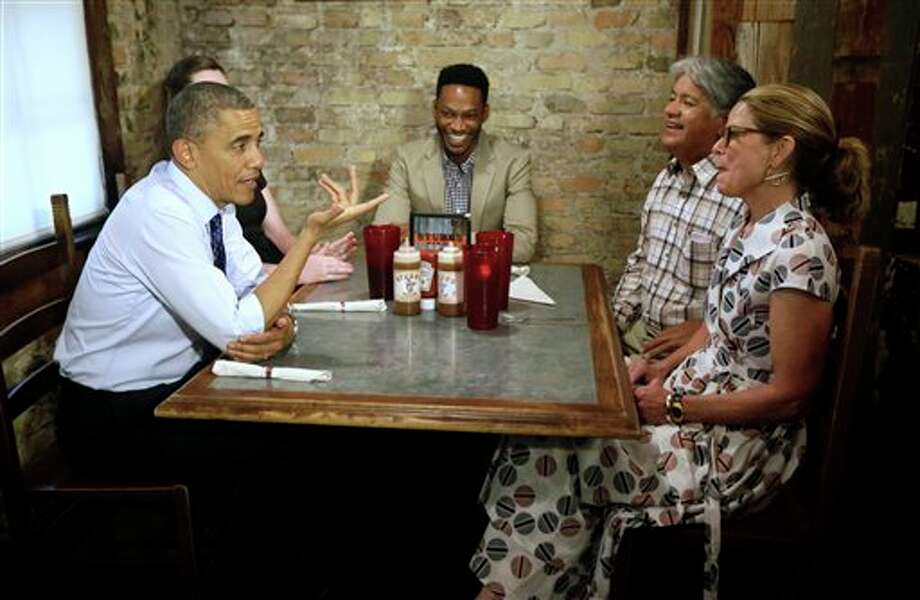 President Barack Obama, left, stops to meets local Austin residence at Stubb's Bar-B-Q restaurant, Thursday, May 9, 2013 in Austin, Texas. Sitting with Obama are from left to right, Caroline Sweet, Tyson Simmons, Joe Alonzo, and Agnes Wommack. (AP Photo/Pablo Martinez Monsivais) Photo: Pablo Martinez Monsivais / AP