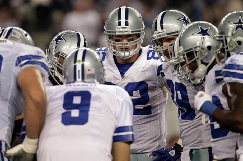 Dallas Cowboys tight end Jason Witten, center, left, and tight end John Phillips, center right, look on at quarterback Tony Romo (9) in the huddle during an NFL football game against the New York Giants Sunday, Dec. 11, 2011, in Arlington, Texas. The Giants won 37-34. (AP Photo/Tony Gutierrez) Photo: Tony Gutierrez / AP