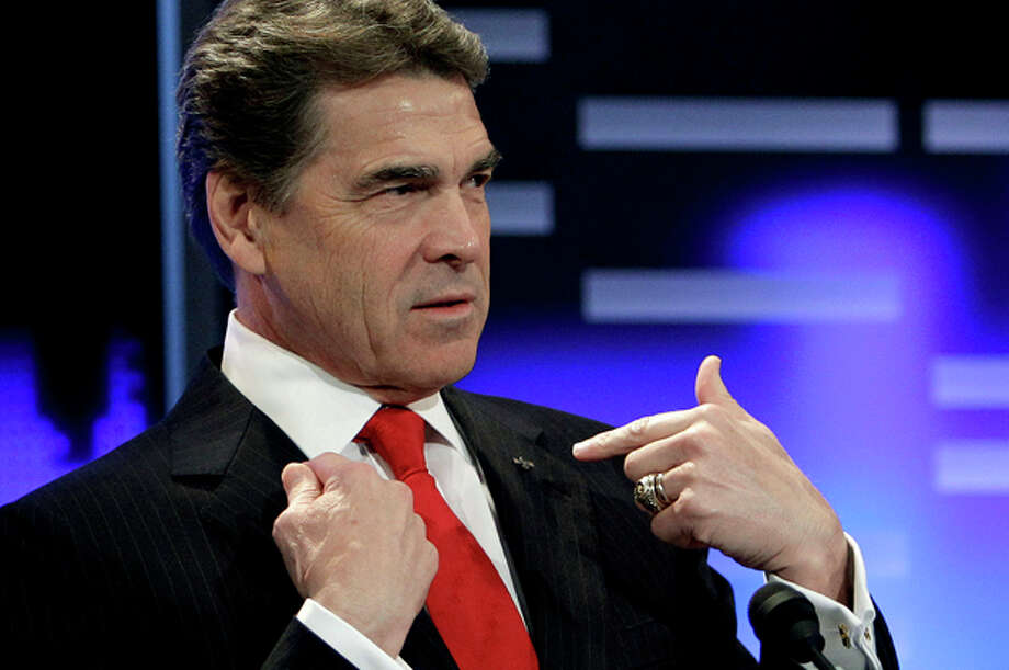 Republican presidential candidate, Texas Gov. Rick Perry stands at his podium as he prepares for the Republican debate, Saturday, Dec. 10, 2011, in Des Moines, Iowa. (AP Photo/Charlie Neibergall) Photo: Charlie Neibergall / AP