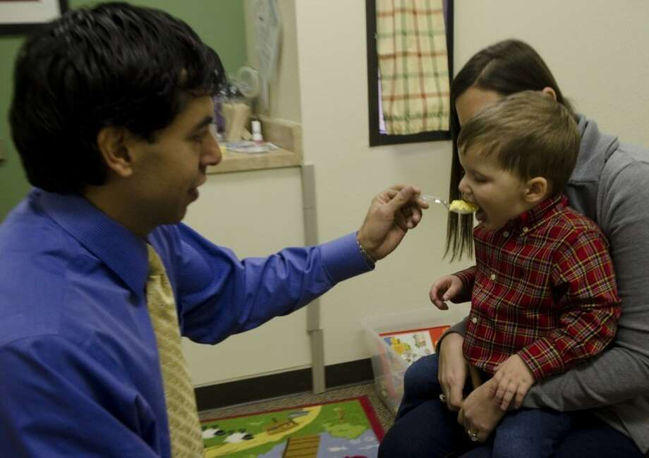 Dr. Miguel Wolbert feeds a spoonful of eggs to 2-year-old Hudson Yeager as his mother, Jennifer, holds him Friday morning. Hudson formerly had an allergy to eggs, causing a rash and vomiting, and Dr. Wolbert has been monitoring him to determine if his allergies has gone away. Photo by Tim Fischer/Midland Reporter-Telegram Photo: Tim Fischer