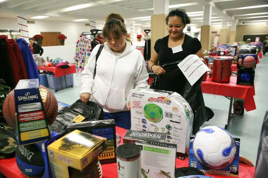 Elva Mejia, left, is assisted by Rocio Perez as she picks out toys for her three children Monday at the First Baptist Church Christmas Store. Cindeka Nealy/Reporter-Telegram Photo: Cindeka Nealy