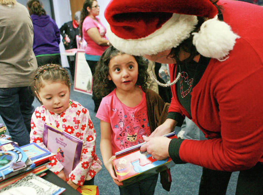 Priscilla Rodriguez's, 5, eyes light as Kids First Director Carol Taylor hands her princess book Wednesday during Operation Elf at Centers for Children and Families. Also pictured is Rodriguez's four-year-old cousin Addison Sanchez. Cindeka Nealy/Reporter-Telegram Photo: Cindeka Nealy
