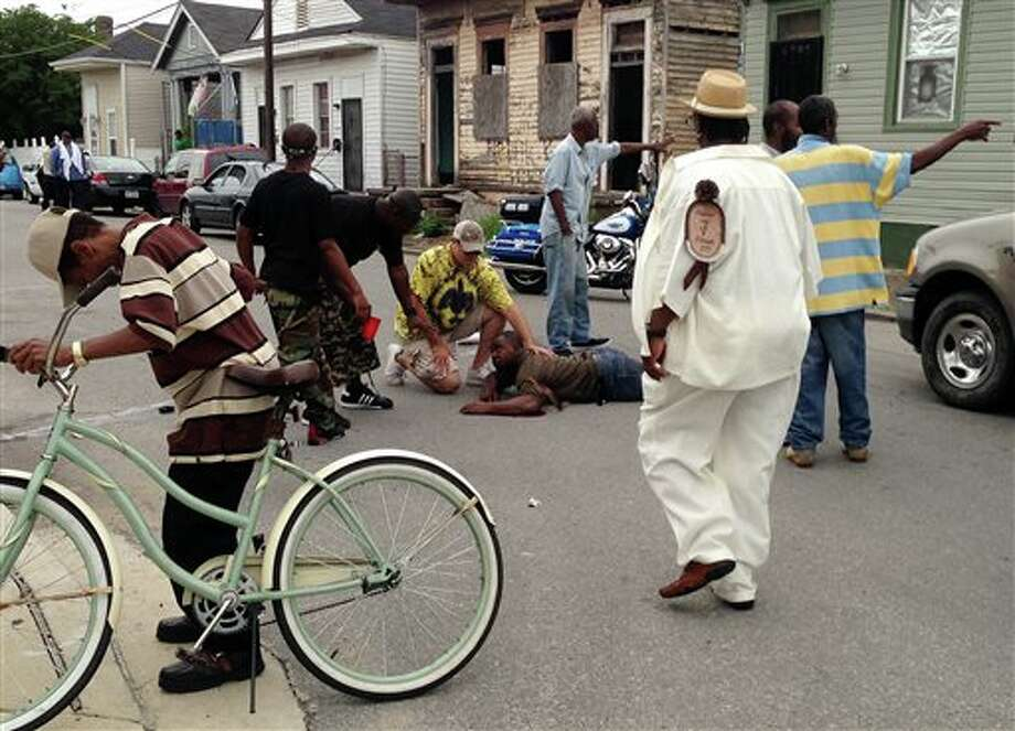 Bystanders comfort a shooting victim while awaiting EMS at the intersection of Frenchmen and N. Villere Streets after authorities say gunfire injured at least a dozen people, including a child, at a Mother's Day second-line parade in New Orleans on Sunday, May 12, 2013. No deaths were reported. (AP Photo/The Times-Picayune, Lauren McGaughy) Photo: Lauren McGaughy  / The Times-Picayune