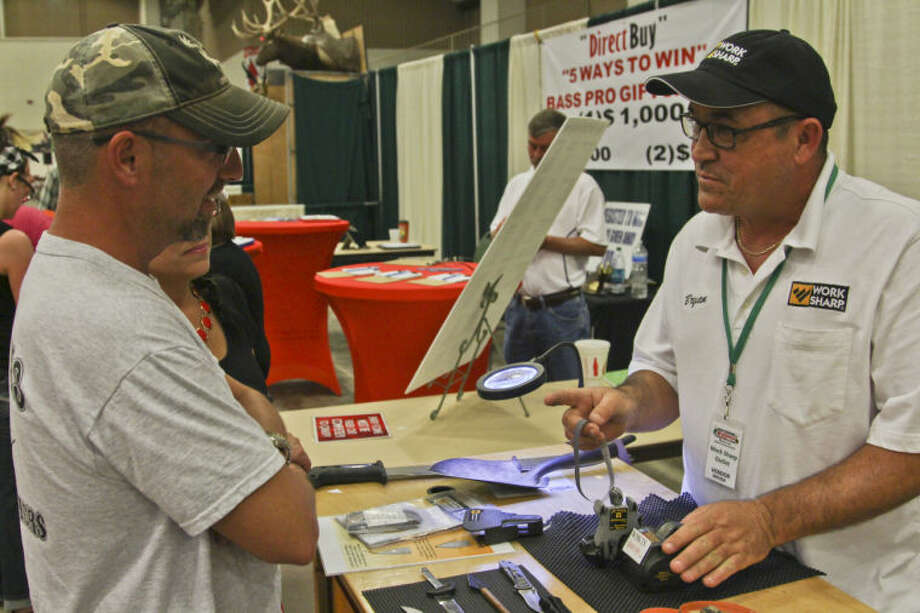 Bryan Eads, right, of Universal City, shows customers how to sharpen a knife Saturday during the Great Outdoors Expo at the Horseshoe. Tyler White/Reporter-Telegram Photo: TYLER WHITE