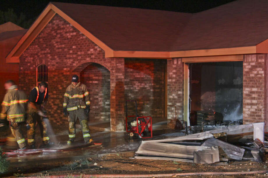 Midland firefighters clean up after breaking through this home's garage door to stop a fire Friday night in the 2900 block of Roosevelt Avenue. Tyler White/Reporter-Telegram Photo: TYLER WHITE