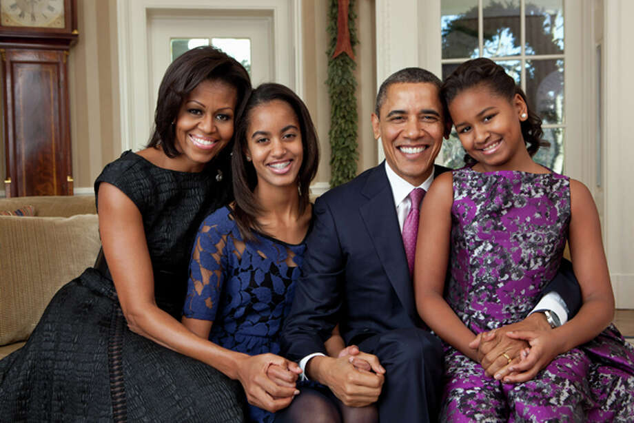 This photo provided by the White House, taken Dec. 11, 2011, shows President Barack Obama, first lady Michelle Obama, and their daughters, Sasha, right, and Malia, center, sitting for a family portrait in the Oval Office of the White House in Washington. (AP Photo/Pete Souza, White House) Photo: Pete Souza / The White House