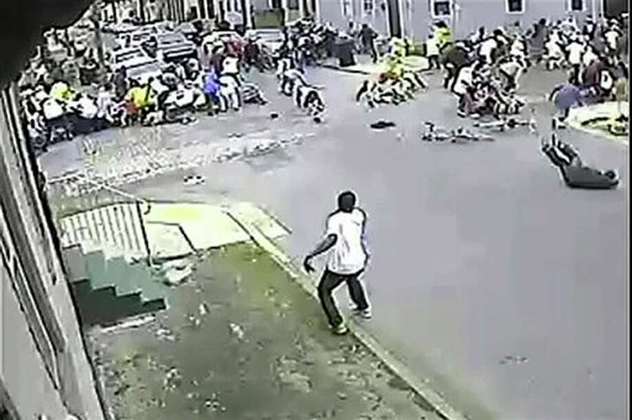 In this image taken from video and provided Monday, May 13, 2013, by the New Orleans Police Department, a possible shooting suspect in a white shirt, bottom center, shoots into a crowd of people, Sunday in New Orleans. Police believe more than one gun was fired in the Mother's Day gunfire that wounded 19 people during a New Orleans neighborhood parade. (AP Photo/New Orleans Police Department) Photo: HOPD / New Orleans Police Department
