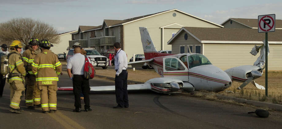 A twin engine Midland College flight training plane crashed Thursday afternoon on Whitmire Boulevardnear Garfield Street. Fire department personnel talk with the pilot, who walked away from the crash. Photo: Tim Fischer/Reporter-Telegram