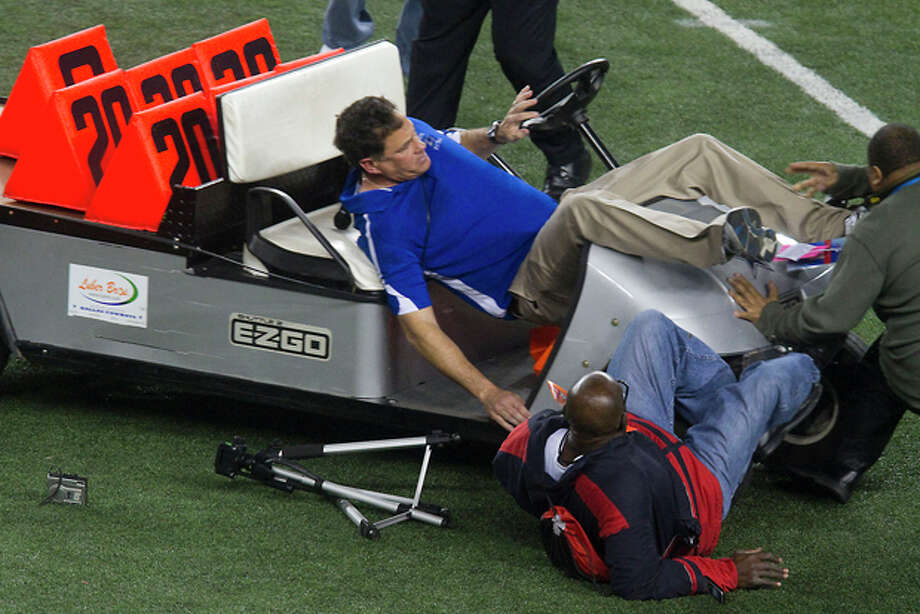 Spring Dekaney head coach Willie Amendola is upended as an out of control cart runs several bystanders over on the Cowboys Stadium field after Spring Dekaney defeated Cibolo Steele 34-14 during the Class 5A Divison II state championships high school football game on Saturday, Dec. 17, 2011, in Arlington, Texas. Two people were taken off the field by stretcher. (AP Photo/The Courier, Patric Schneider) Photo: Patric Schneider / AP