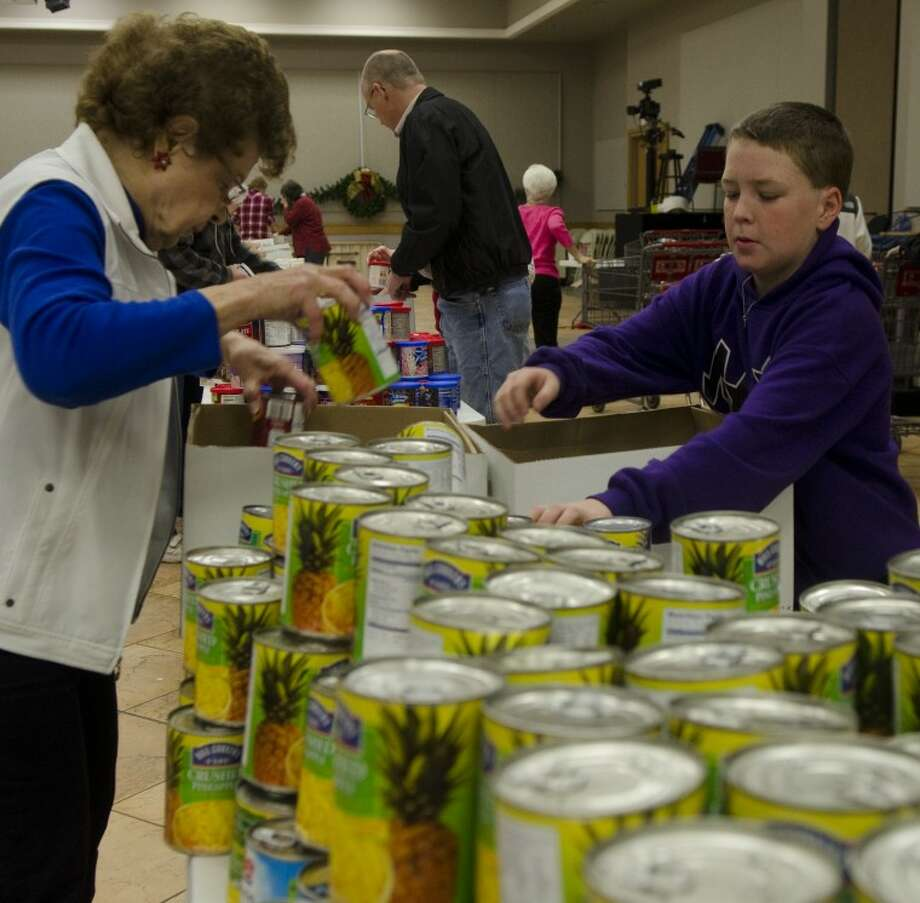 Fran McGilvray, Bryce Lewis and other volunteers load boxes with food items to be delivered to area families as part of First Baptist Church's White Christmas. All the extra food items will be given to the Midland Soup Kitchen and Meals on Wheels. Photo: Tim Fischer/Reporter-Telegram