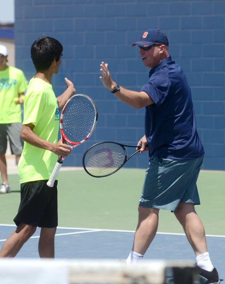 Former professional tennis player Luke Jensen high fives Jonathan Dorman, a Midland Christian student, while the two play a doubles match during the grand opening of the Bush Tennis Center Saturday at the Center. James Durbin/Reporter-Telegram Photo: JAMES DURBIN
