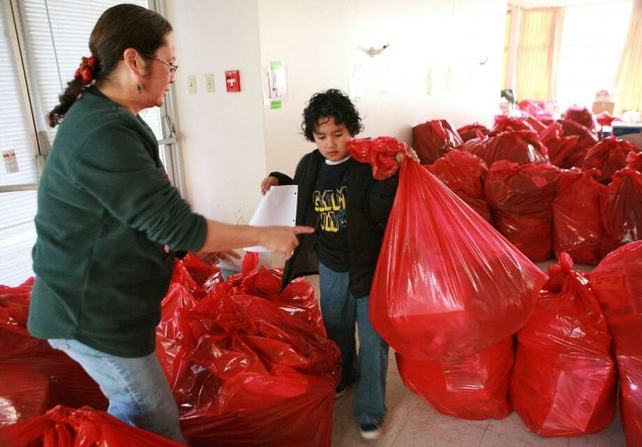 Teresa Stickel assists Xavier Hernandez, 7, with finding bags of toys to hand out to waiting clients Tuesday during the Salvation Army's Christmas program distribution at Trinity Towers. Photo: Cindeka Nealy/Reporter-Telegram