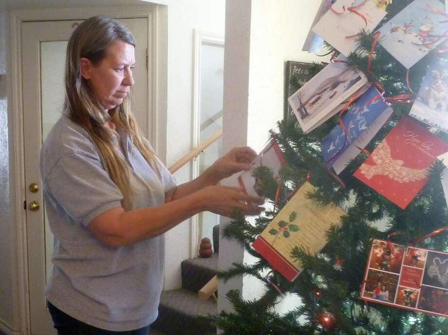 "Debbie Ellinger, of Pet Solution Inc., hangs cards on the nonprofit's Christmas tree Tuesday afternoon. Ellinger started a ""Cards for Critters"" campaign this year and asked anyone who was willing to send a Christmas card with $1 inside to support an expansion of the pet rescue outreach they run. They've received cards from throughout the state and country. Photo: Kathleen Thurber/Reporter-Telegram"