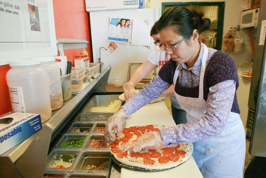 Diana Wang prepares a pizza Wednesday at MD Pizza. Wang and her husband Matt Tseng don't live near their family and their customers are like family so they will open on Christmas day to give them to option of eating out instead of cooking. Cindeka Nealy/Reporter-Telegram Photo: Cindeka Nealy