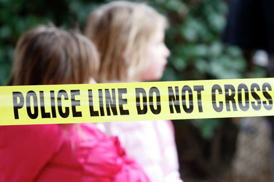 Two young girls walk by police tape that stretches through a Grapevine, Texas, apartment complex where police found seven people dead in an apartment on Sunday, Dec. 25, 2011 in Grapevine, Texas. Four women and three men who police believe to be related were found apparently shot to death, and authorities said they believe the shooter is among the dead. (AP Photo/Mike Fuentes) Photo: Mike Fuentes / FR103746 AP