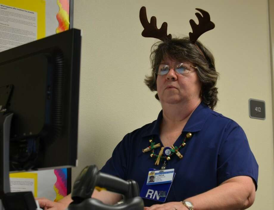 Linda Harlow checks patients' medical and drug records Christmas afternoon. Harlow is a registered nurse in the oncology department at Midland Memorial Hospital and volunteered to take the holiday shift to bring joy to those who are ill. Photo: James Cannon/MRT