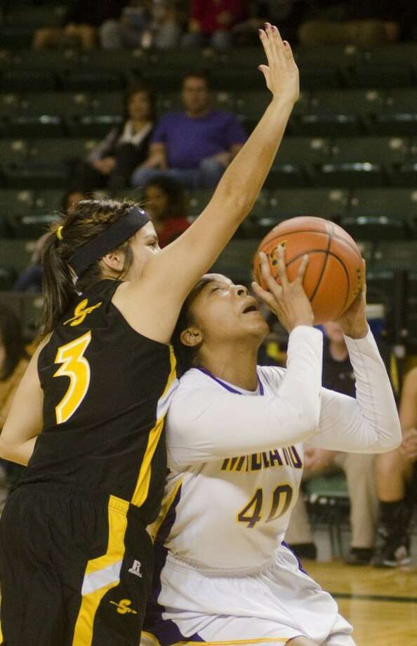 Midland High's Sabrina Banks is fouled by Seminole's Kaleen Sarli as she goes for a shot Wednesday evening at the Byron Johnston Holiday Classic tournament at the Chaparrel Center. Photo by Tim Fischer/Midland Reporter-Telegram Photo: Tim Fischer