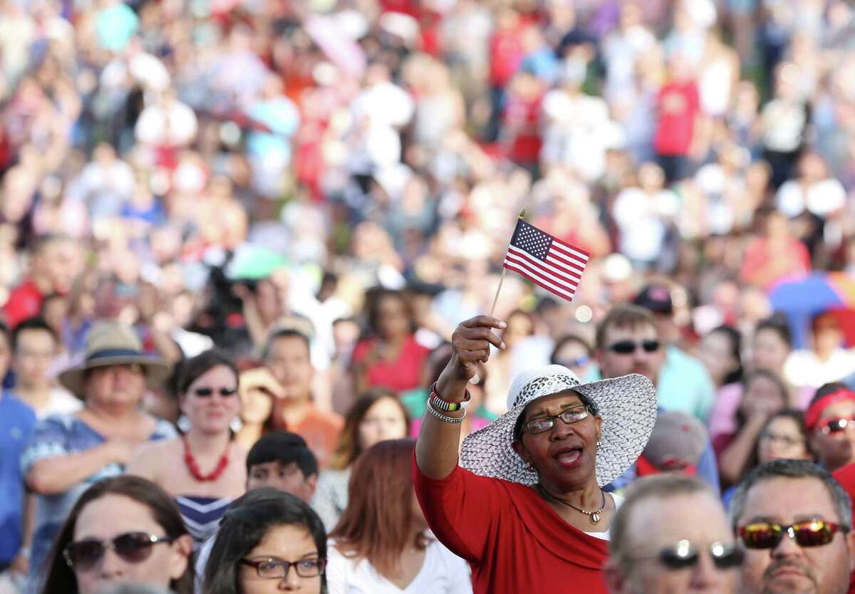 Bessie Taiwo sings along with the national anthem at Freedom Over Texas at Eleanor Tinsley Park and Sam Houston Park Saturday, July 4, 2015, in Houston. Taiwo said she wanted to celebrate the nation. ( Jon Shapley / Houston Chronicle )