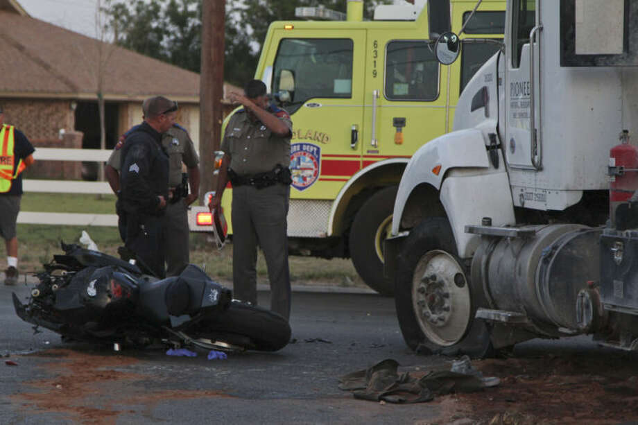 Law enforcement officials worked to clean up the aftermath of this head-on collision involving a motorcycle and 18-wheeler Wednesday at the intersection of South County Road 1130 and Farm-to-Market Road 307. Tyler White/Reporter-Telegram Photo: TYLER WHITE