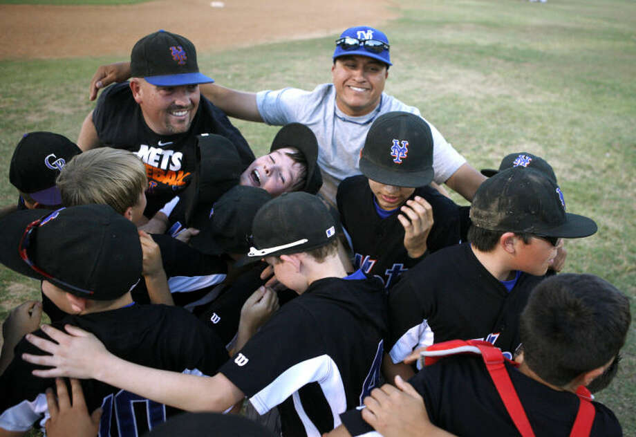 The Mets' Little League team shares a group hug after beating the Dodgers 7-4 in the National League City Tournament Final on Wednesday at Mid City Park. James Durbin/Reporter-Telegram Photo: JAMES DURBIN