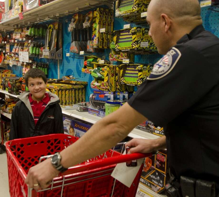 Micheal, 11, from Big Spring, eyes MPD Officer Jimmy Young Monday while shopping at Target with the Shop with a Cop program. Micheal admitted at the begining he did not like police, but ended up changing his mind after the shopping spree. Photo: Tim Fischer/ Reporter-Telegram