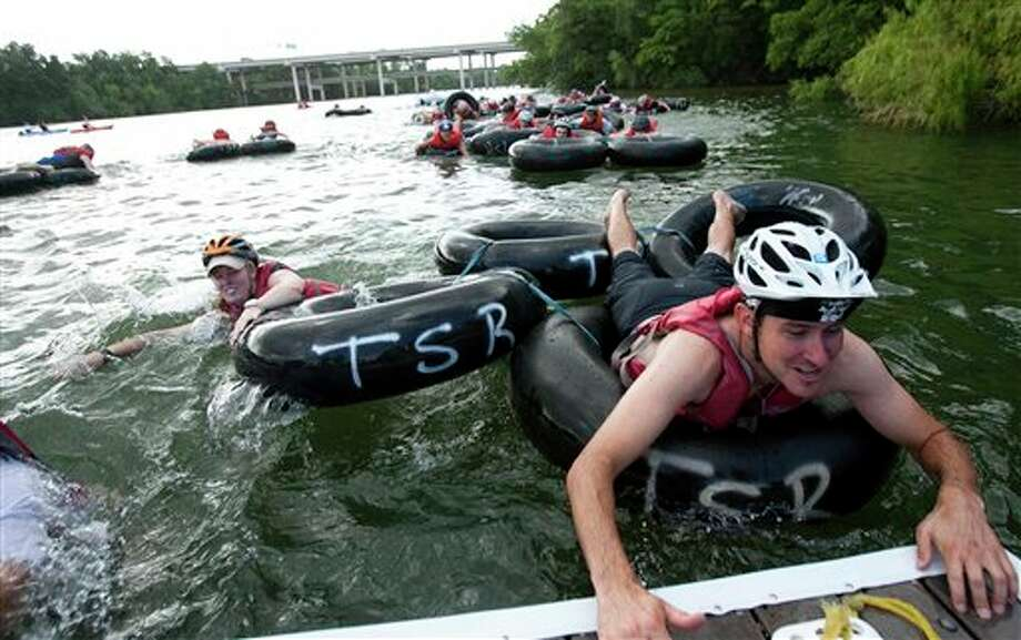 Participants climb out of a raft made of inner tubes that they had to navigate around an inflatable whale at one of the obstacle stops on a rowing dock during the New Belgium Urban Assault Ride, in Austin, Texas on Sunday, June 26, 2011.  (AP Photo/Austin American-Statesman, Kelly West) Photo: Kelly West / Austin American-Statesman