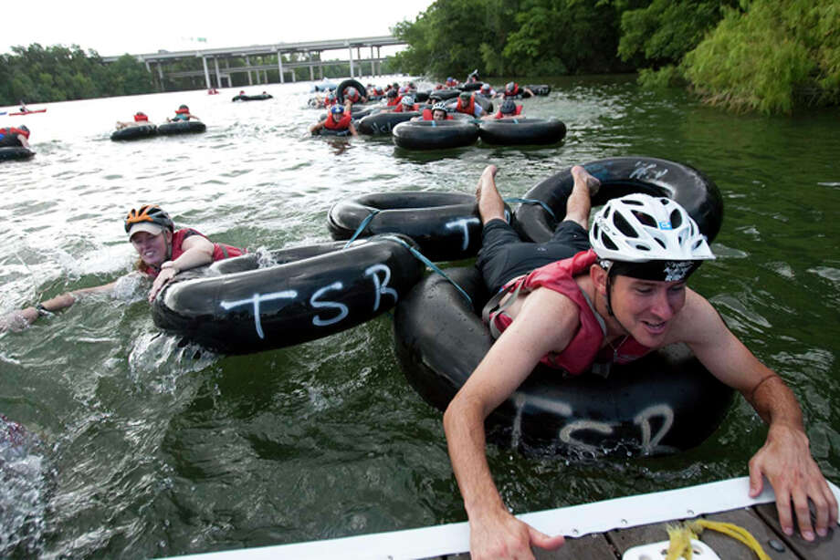 Participants climb out of a raft made of inner tubes that they had to navigate around an inflatable whale at one of the obstacle stops on a rowing dock during the New Belgium Urban Assault Ride, in Austin,  June 26. Photo: Kelly West/Austin American-Statesman / Austin American-Statesman