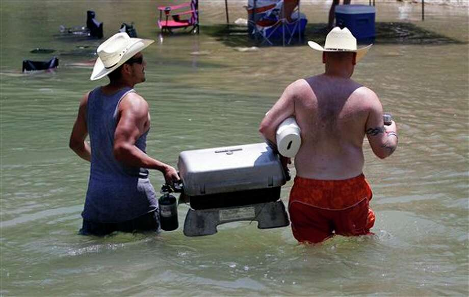 In this Friday, July 15, 2011 photo, Jose Vargas, left, and Kevin Aldridge, right, carry a grill across the Guadalupe River, in New Braunfels, Texas. Photo: Eric Gay/AP / AP