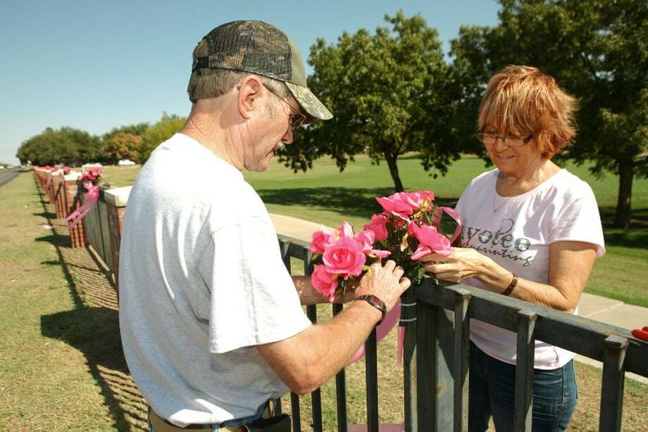 Cherrie Wilson, a breast cancer survivor, and her husband Jim decorate the fence along Grafa Park with pink flowers and bows to help raise awareness. Cindeka Nealy/Reporter-Telegram Photo: Cindeka Nealy