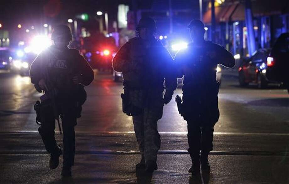 Officers wearing tactical gear arrive at the Watertown neighborhood of Boston, Friday, April 19, 2013. Reports of explosives being detonated and police are telling reporters to turn off their cell phones. Dozens of officers and National Guard members are in Watertown, where television outlets report that gunfire and explosions have been heard. (AP Photo/Julio Cortez) Photo: Julio Cortez / AP