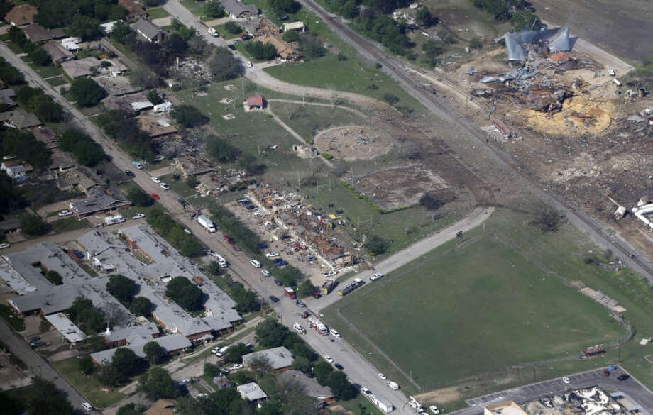 This Thursday, April 18, 2013 aerial photo shows the remains of a nursing home, left, apartment complex, center, and fertilizer plant, right, destroyed by an explosion in West, Texas. Rescuers searched the smoking remnants for survivors of Wednesday night's thunderous fertilizer plant explosion, gingerly checking smashed houses and apartments for anyone still trapped in debris while the community awaited word on the number of dead. Initial reports put the fatalities as high as 15, but later in the day, authorities backed away from any estimate and refused to elaborate. More than 160 people were hurt. (AP Photo/Tony Gutierrez) Photo: Tony Gutierrez